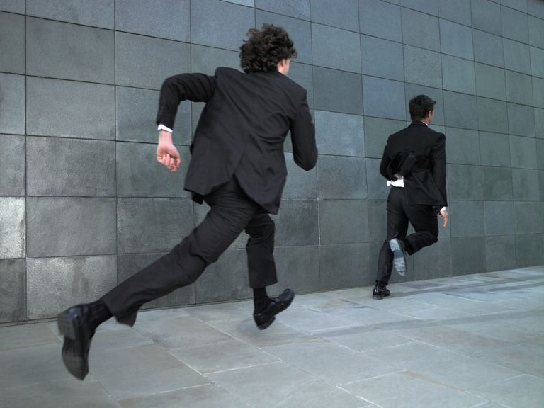 Businessmen chasing each other