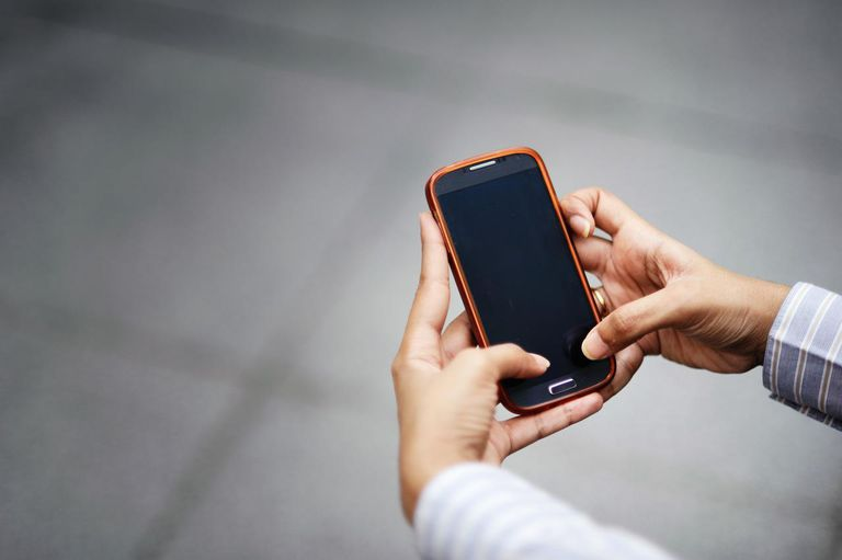 Woman's hands holding an orange smart phone