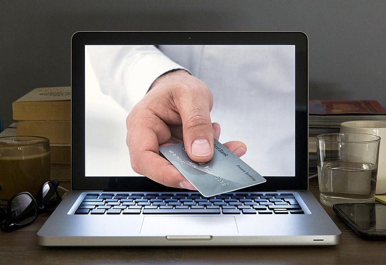 Hand holding credit card appearing from laptop