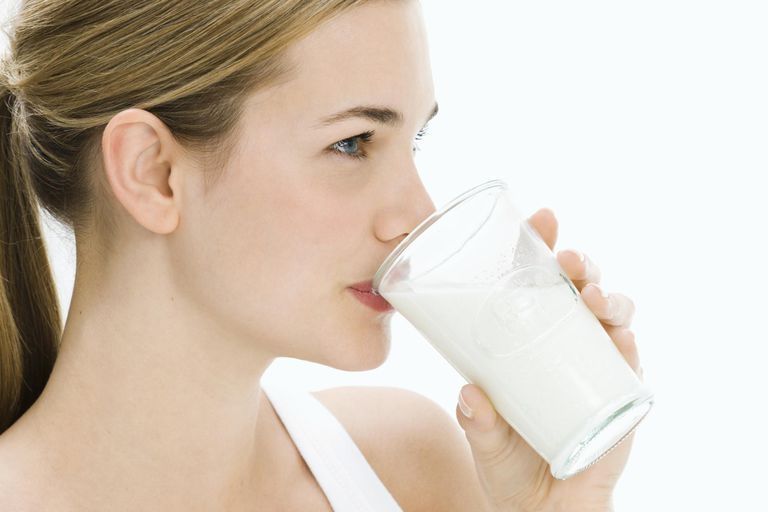 Woman drinking glass of milk, side view