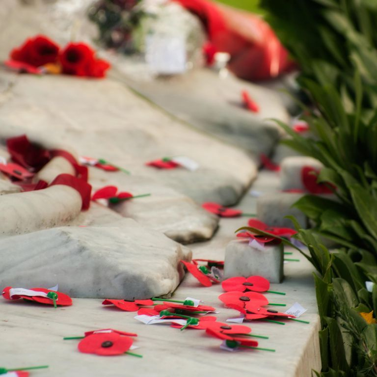 Anzac poppies and wreathes on a war memorial on Anzac Day.