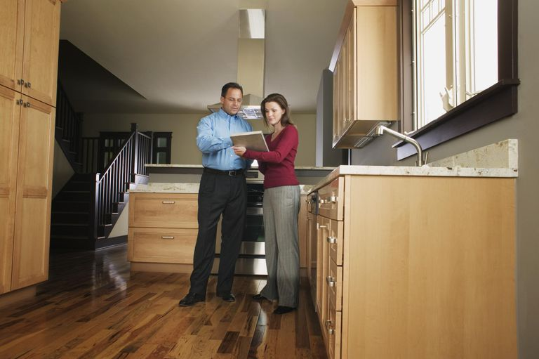 Man and woman standing in kitchen reading document