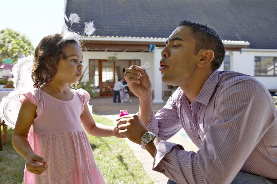 A father and daughter blowing bubbles