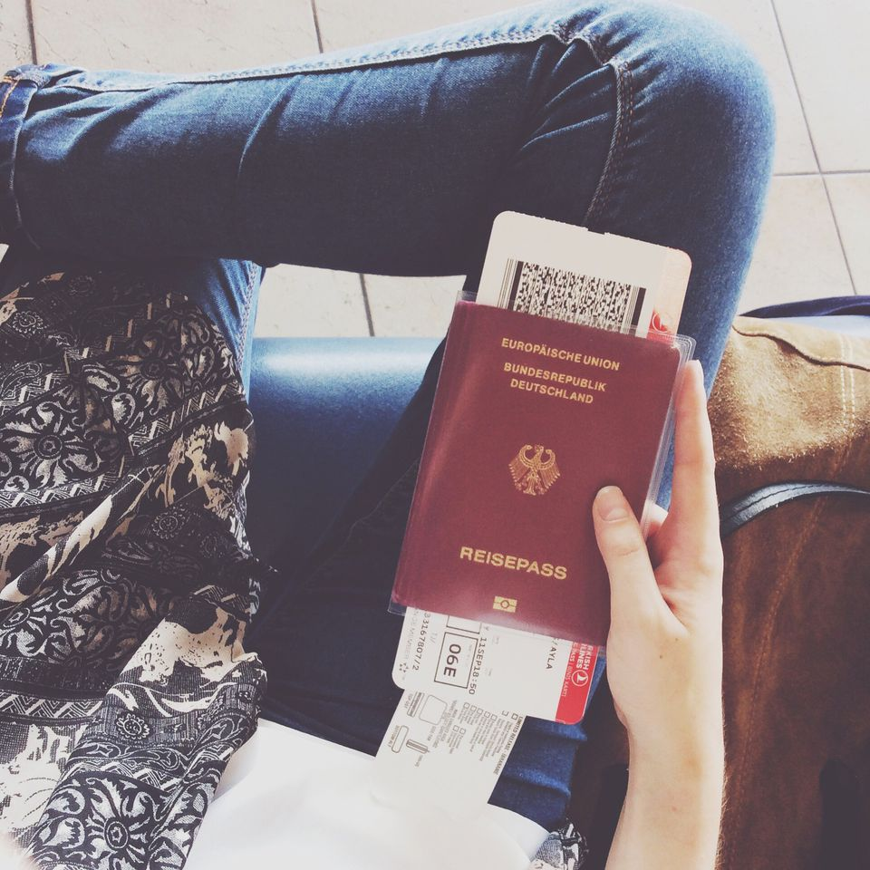 woman holding boarding pass and passport