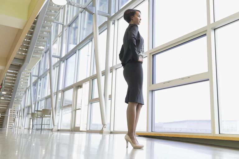 Full length businesswoman looking out window