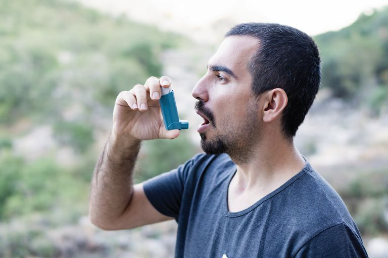 What happens during an asthma attack. Young man using an asthma inhaler