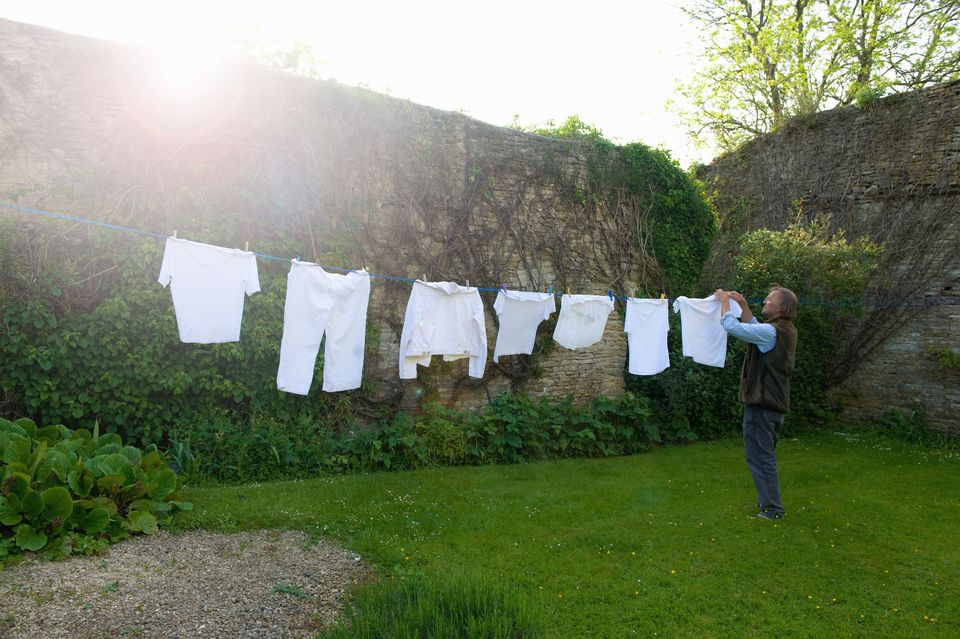Man standing on a lawn in a garden, hanging up laundry on washing line.