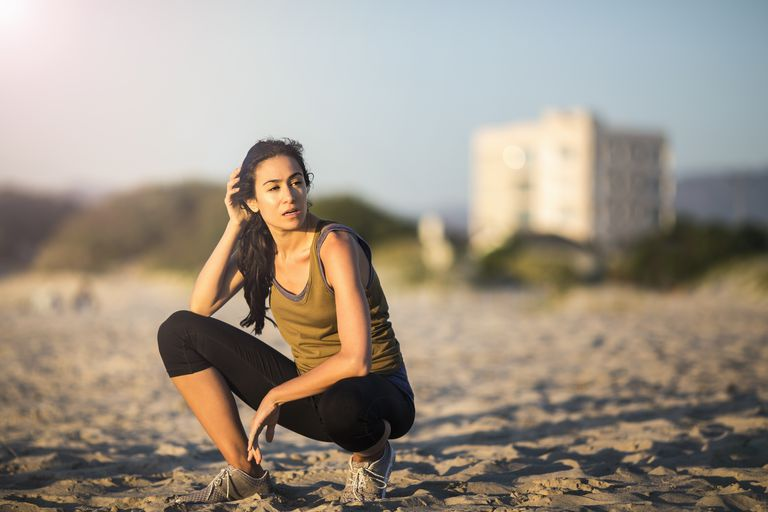 Tired young female athlete crouching at beach