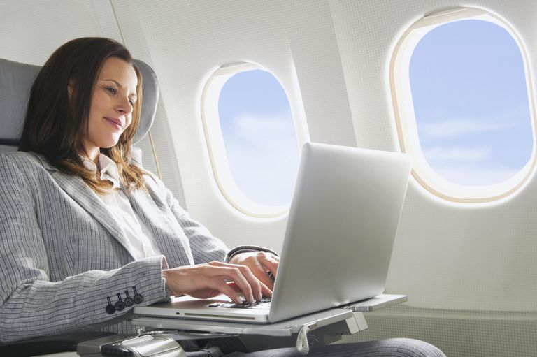 Adult businesswoman using laptop in business class airplane cabin