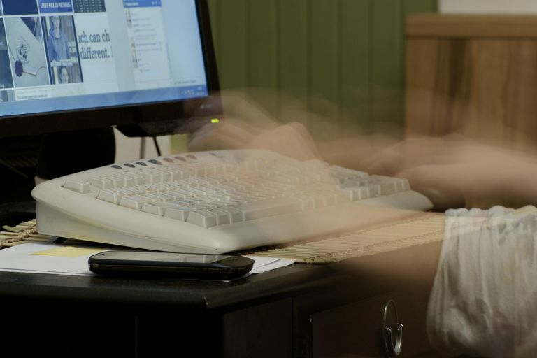 Photo of a person typing quickly.