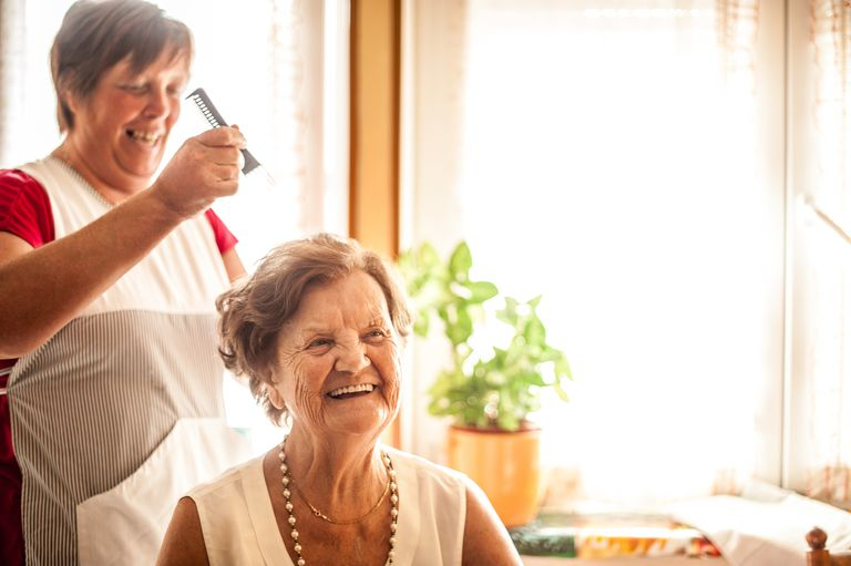 Caregiver combing hair of woman with Dementia.