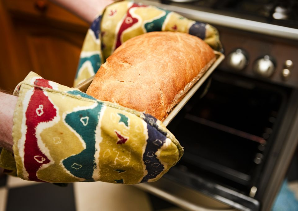 Using oven mitts to remove oven baked bread