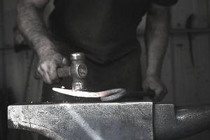 A blacksmith shaping a hot piece of iron on an anvil using a hammer.