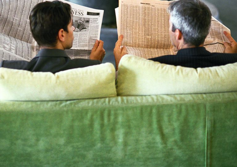 Two men reading the newspaper looking for IRA rates.