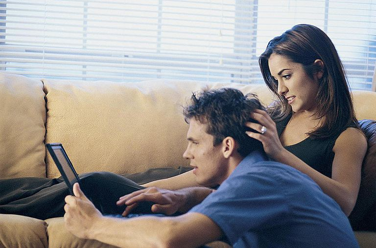 Couple using computer together at home