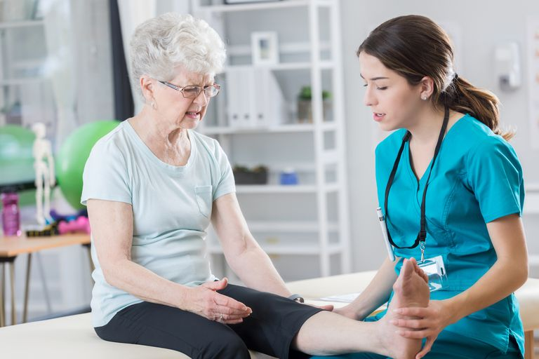 Young doctor examines senior patient's leg