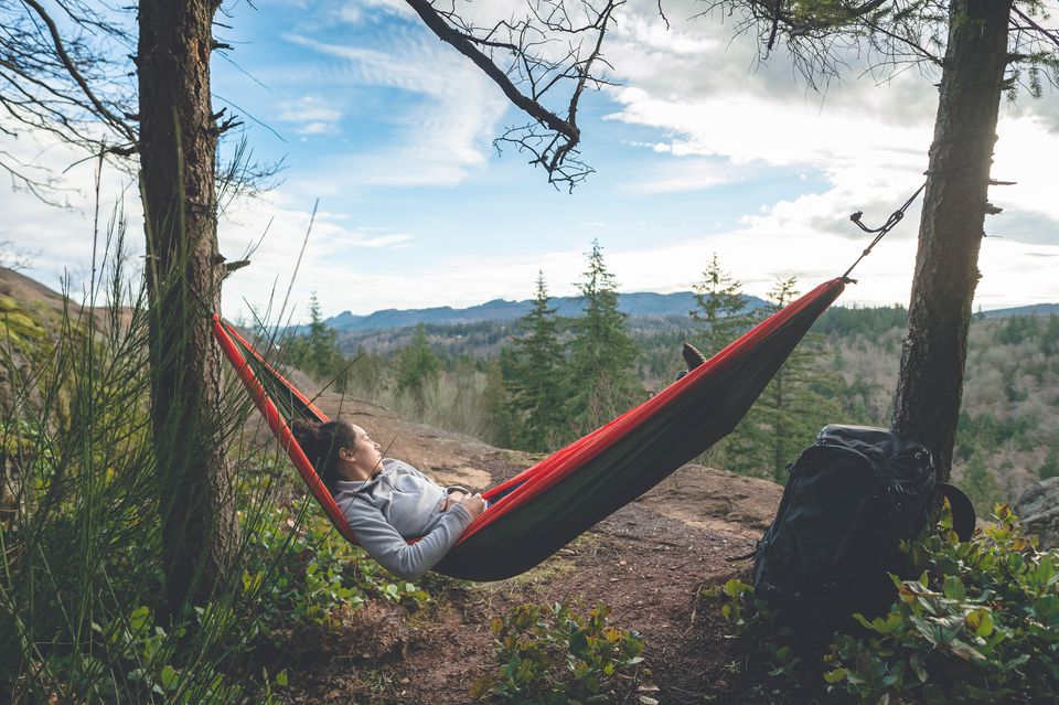A woman in a hammock in a forest.
