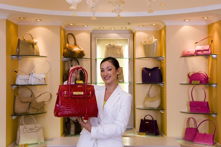 Young woman standing in front of shelf display in glamorous boutique, holding red designer handbag, smiling, front view, portrait