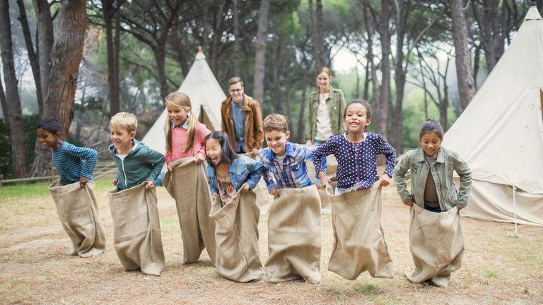 Staff de campamentos y niños jugando a saltar dentro de un saco