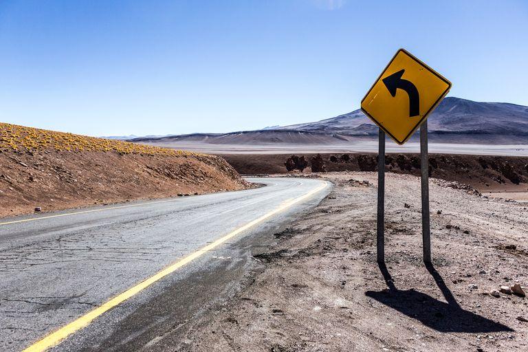 Empty Road And Sign Against Sky At Atacama Desert