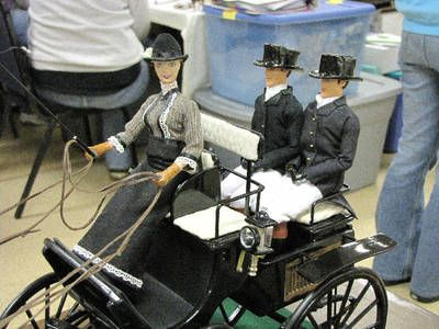 Model horse carriage with a driver and two passengers.