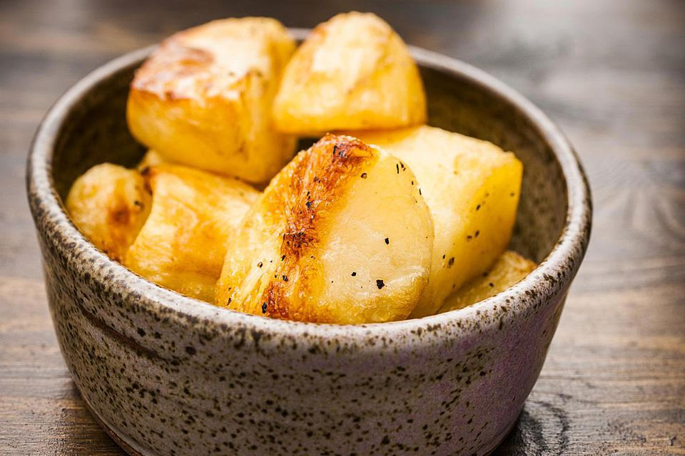 Bowl of golden roasted potatoes.