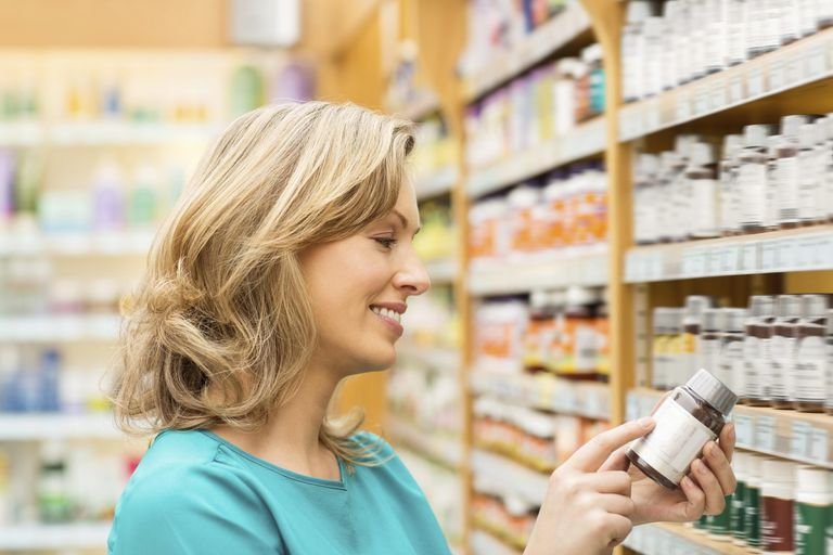 Woman Reading Instructions On Pill Bottle