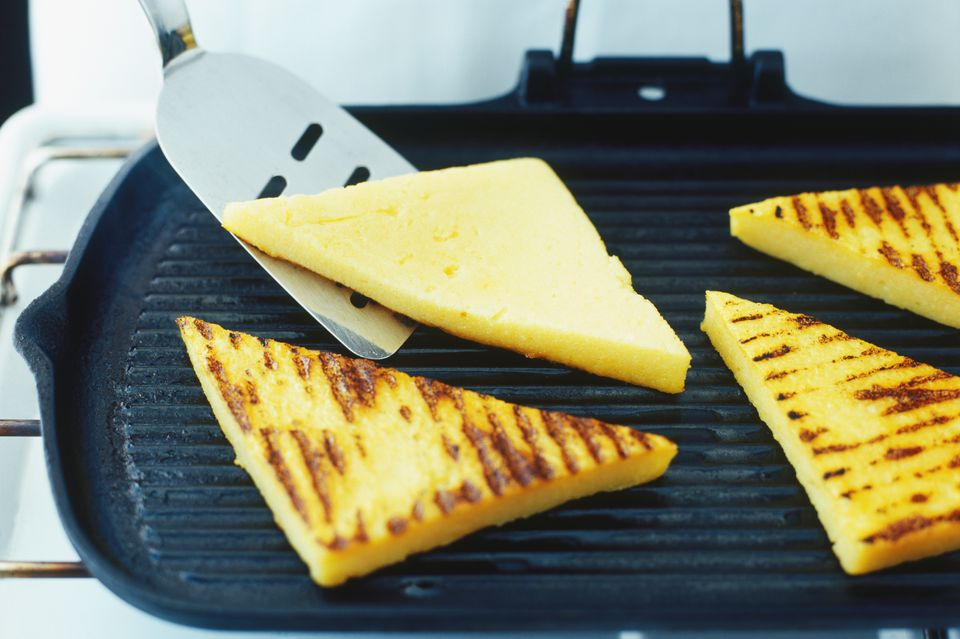 Grilled polenta triangles cooking on a ridged grill pan