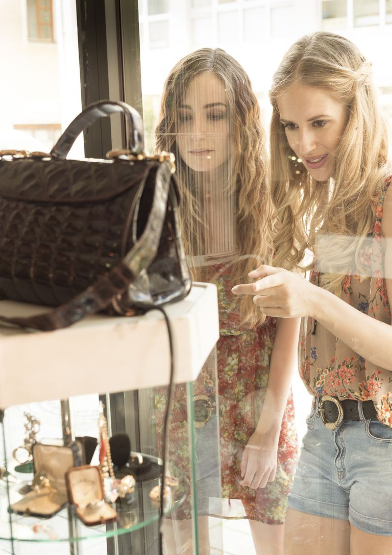Two female friends looking through window of an antique shop