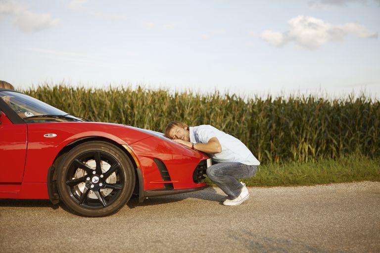 Man Hugging His Electric Car