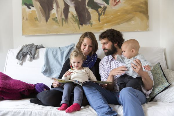 Young family reading storybook together on sofa