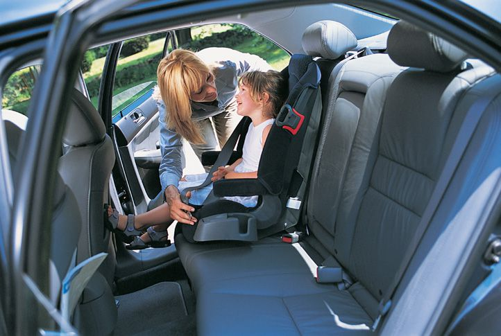 A mother fastening her child into a booster seat.
