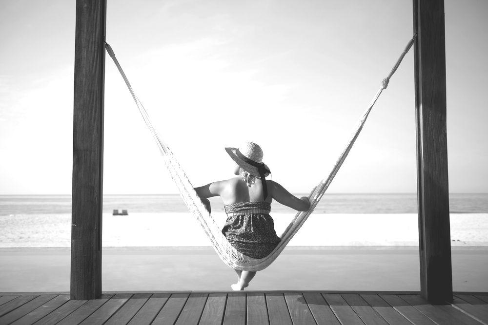 Woman sits in hammock facing the beach