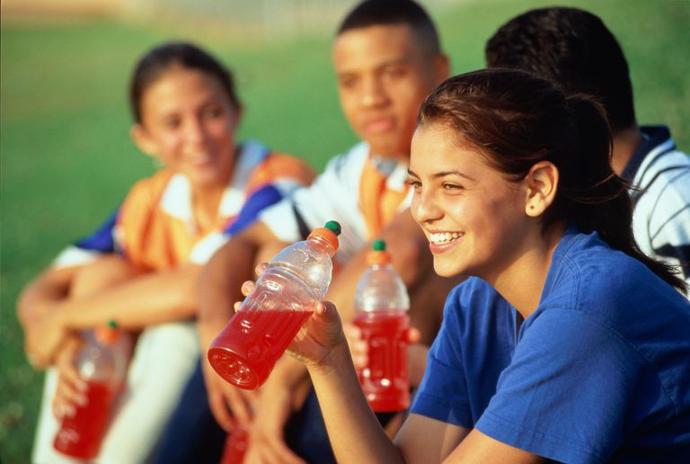 Teenagers (14-16) resting with drinks after football game