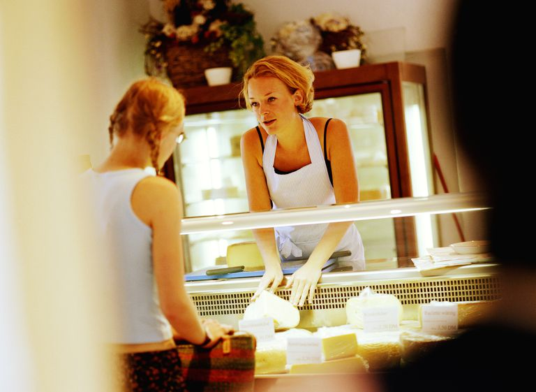 Young woman serving customer at cheese counter