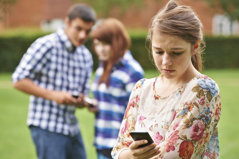 upset teen girl looking at cell phone with other teens in background