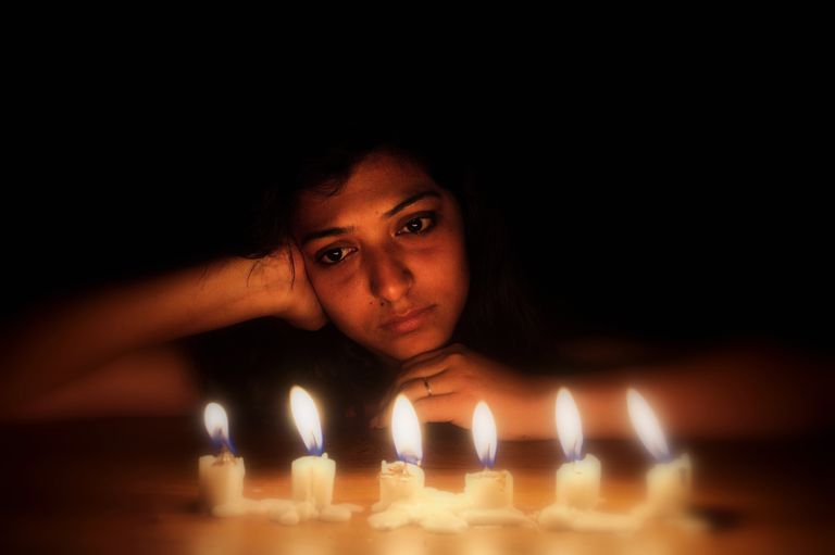 Illuminated Candles Against Thoughtful Woman Leaning On Table In Darkroom