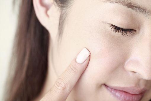 Young woman touching blush, close-up, beauty care