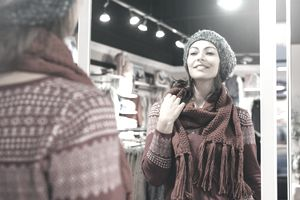 woman trying out a scarf in a retail store