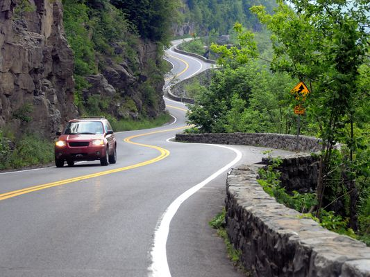 The winding Route 97, outside of Port Jervis, NY, late afternoon in Summer just before a storm, with an approaching car with its headlights on.
