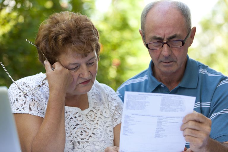 A senior couple reads a bill