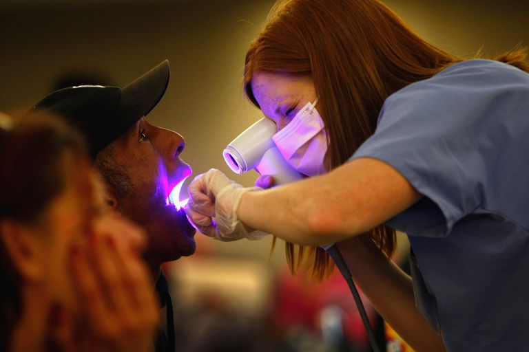 dental hygienist screens man for oral cancer at a free clinic
