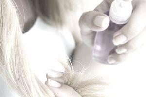 woman applying tonic hair care spray on hair ends