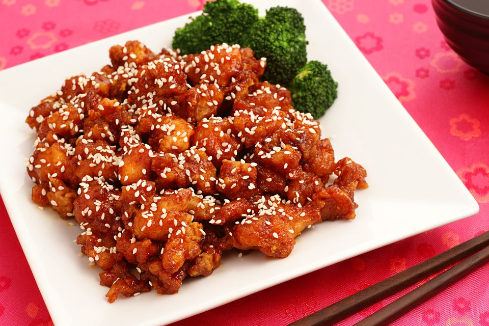 Sesame chicken with broccoli on square plate on red table