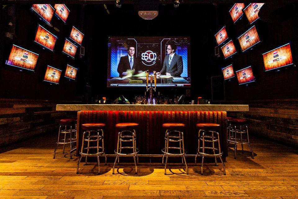 Bar stools and TVs at a sports bar