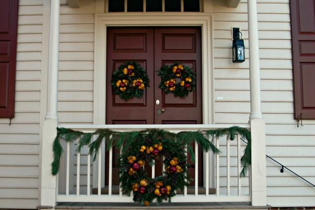 Entryway wreaths and evergreen boughs like those at Colonial Williamsburg suit the traditional Christmas decorating style.