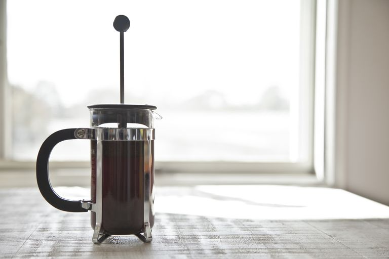 French press full of coffee sitting on a table