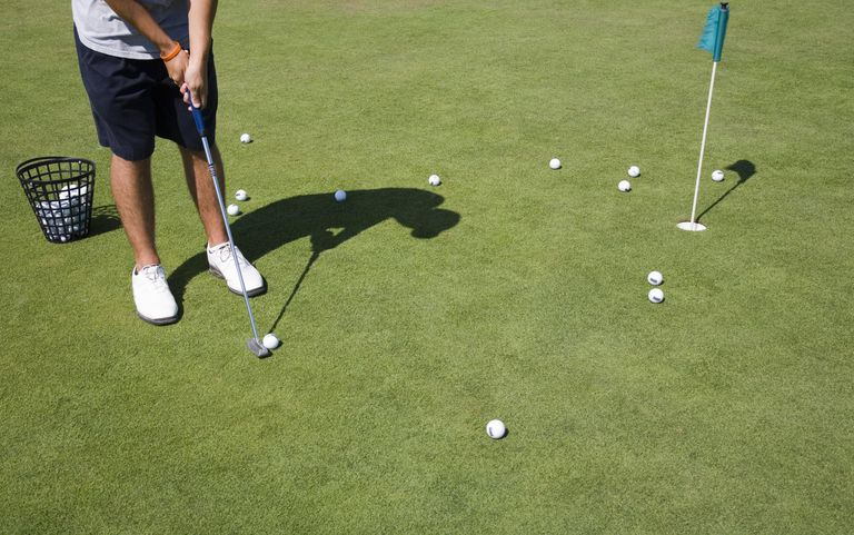 Golfer practicing on putting green, low section