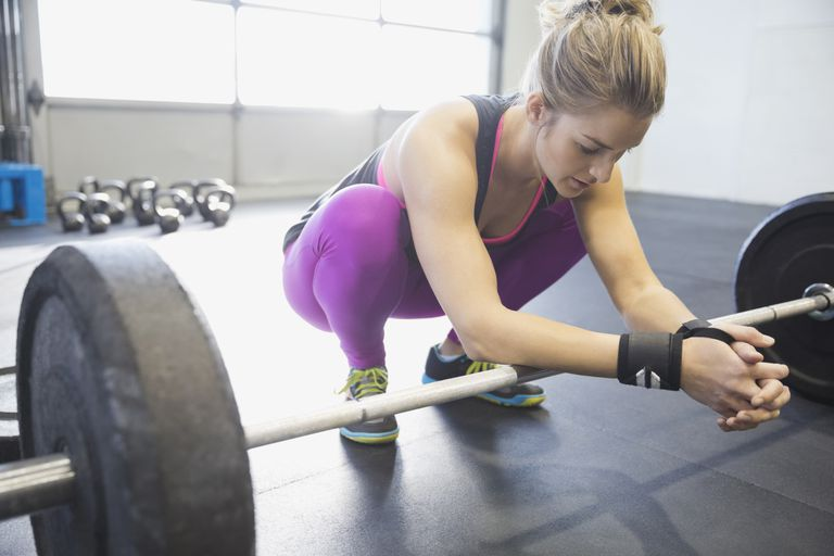tired female weight lifter resting on barbell