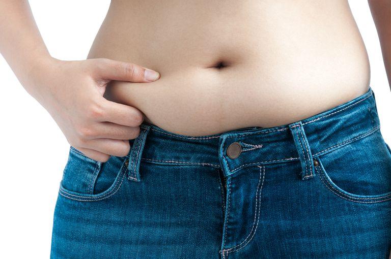 Woman pinching belly fat in jeans